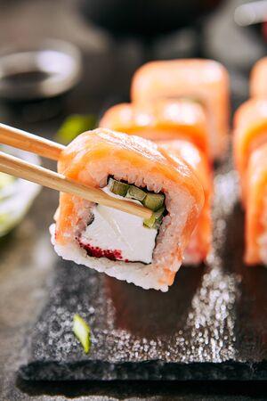 Beautiful Philadelphia Sushi Rolls Set with Salmon and Cream Cheese, Tobiko and Cuccumber on Black Slate Plate Close Up. Uramaki, Nori Maki or Futomaki Sushi with Trout Fillets, Soy Sauce and Wasabi