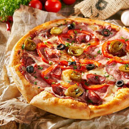 피자 레스토랑 메뉴 - 소시지와 칠리 페퍼를 곁들인 맛있는 매운 피자. 재료와 소박한 나무 테이블에 피자