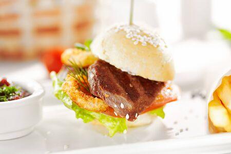 Gourmet, Restaurant, leckeres Abendessen - Nahaufnahme von Sandwich mit Rindfleisch und frittierten Zwiebeln, Tomate und Gurke. Garniert mit Pommes Frites