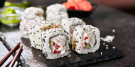 Macro shot of chicken uramaki sushi with bacon, processed cheese, tomato, green onion, black and white sesame, nori. Rainbow sushi rolls on natural black slate background with selective focus closeup 写真素材