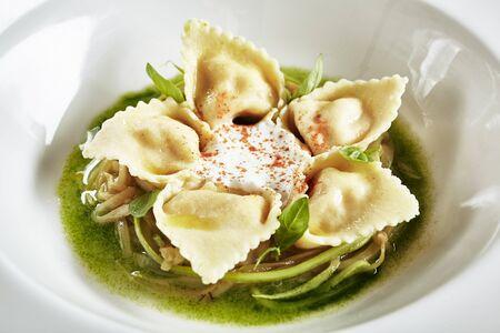 Hermoso restaurante blanco que sirve plato de tortellini con camarones y ragú de calabacín joven. Exquisito plato italiano molecular creativo con ravioles de mariscos sobre piedra negra natural