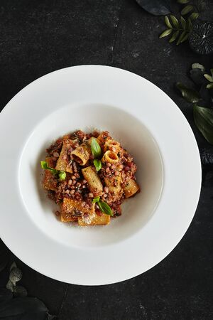 Exquisite Serving White Restaurant Plate of Homemade Rigatoni with Bolognese Sauce and Smoked Pork Belly Top View. Stylish High Kitchen Italian Penne Pasta Tubes on Natural Black Marble Background