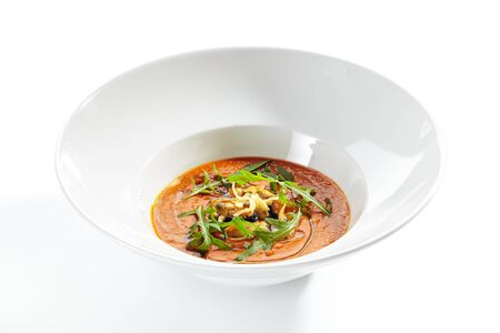 Exquisite serving spicy tomato soup with fried mussels and chili pepper on white restaurant plate isolated. High cuisine delicious seafood gazpacho with greens and spices in minimalist style Stock fotó