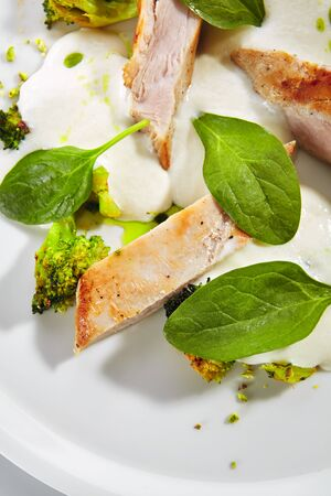 Exquisite serving fried turkey fillet with baked broccoli cabbage, spinach leaves and cheese espuma on white restaurant plate isolated. High cuisine restaurant dish with barbecue meat closeup