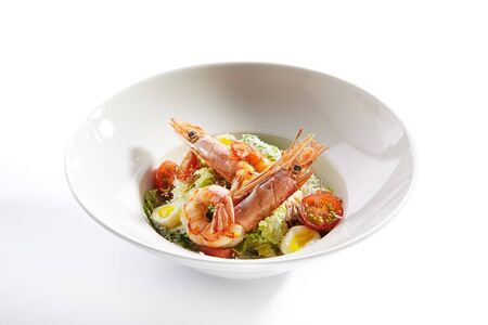 Delicious caesar with argentinian shrimps closeup. North american cuisine restaurant dish, menu item. Tasty salad with natural seafood isolated on white background. Organic lunch, healthy food Stockfoto