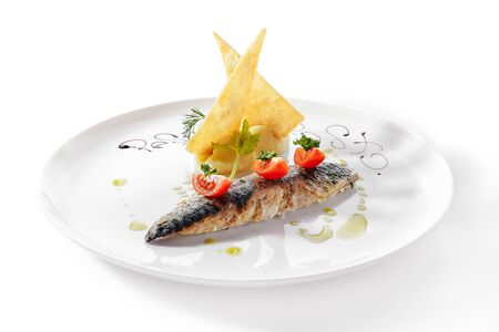 Exquisite serving grilled mackerel with mashed potatoes and tomatoes on white restaurant plate closeup.