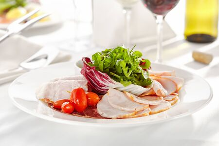 Gourmet, restaurant, delicious dinner food - close up of Sliced Meats with Rocket Salad and Tomatoes Foto de archivo