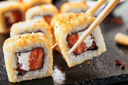Taking portion of hot crispy tempura maki sushi rolls with cream cheese, raw salmon, tomato and nori seaweed. Deep fried uramaki roll set on natural black stone slate background closeup Banco de Imagens