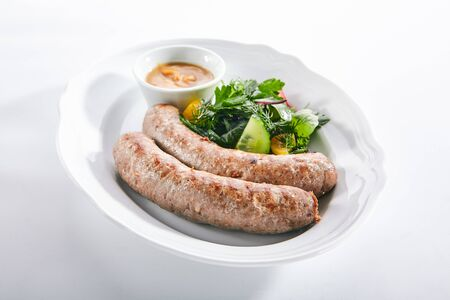 Macro shot of Munich sausages for frying made from pork and beef with mustard sauce and mixed salad isolated. Traditional German rostbratwurst, wurst or bratwurst with vegetables and greens closeup