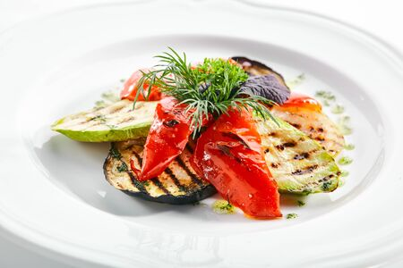 Beautiful serving white restaurant plate of grilled vegetables and fresh greens isolated. Barbecue eggplant, zucchini and sweet red bulgarian pepper with dill and pesto sauce closeup Banco de Imagens