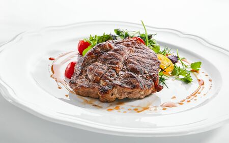 Macro shot of pork neck steak with mixed salad on white restaurant plate isolated. Restaurant main course with well done meat, veal or beefsteak with tomatoes, fresh parsley, dill and chard closeup