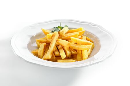 Macro shot of fries or french fries on white restaurant plate isolated. Sweet potato finger chips, french-fried potatoes, delicious fast food with salt and a leaf of parsley closeup