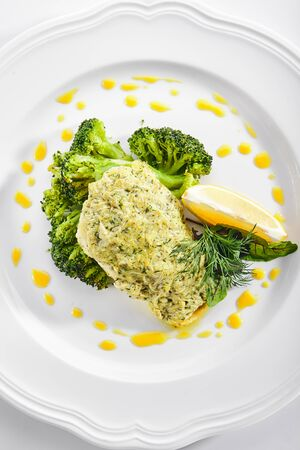 Top view of pike perch or zander fillet in cream sauce with broccoli isolated. Restaurant main course with fried sander fish or pike meat with lemon and greens top view Banco de Imagens