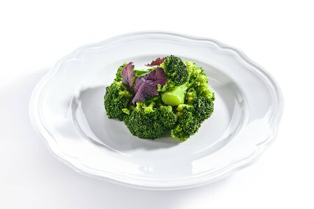 Macro shot of steamed broccoli on white restaurant plate isolated. Green asparagus cabbage cooked on steam, healthy veggie vegetables in vegan restaurant closeup