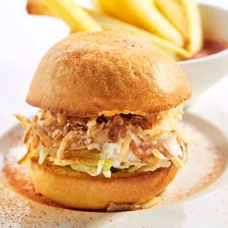 Burger with crab meat and french fries closeup. Fast food restaurant dish, menu item. Tasty snack, delicious appetizer isolated on white background. Sandwich with fried potato and sauce closeup