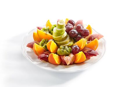 Macro shot of fruit plate with orange wedges, apple, grapes, kiwi and pear isolated. Vegan platter with sweet sliced fruits, healthy and delicious breakfast closeup