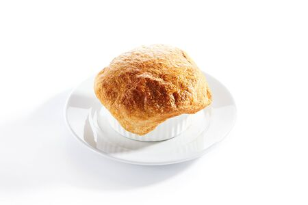 Macro shot of julienne or potage soup with chicken and mushrooms topped with melted cheese or puff pastry on white restaurant plate isolated. Stew baked in white bowl with bread on top closeup