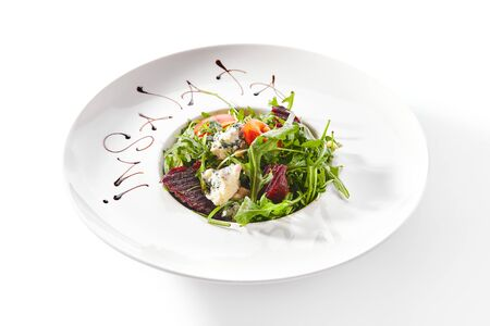 Macro shot of salad with beetroot, rucola and Gorgonzola cheese on white restaurant plate isolated. Veggie salat bowl with cooked beets, fresh arugula and tomatoes closeup Stok Fotoğraf