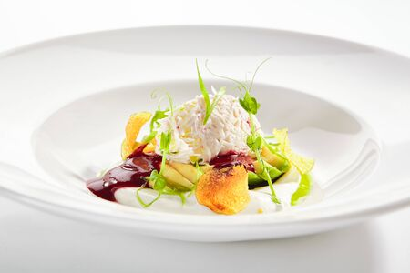 Exquisite serving avocado salad with truffle and crab on white restaurant plate isolated. Luxury gourmet restaurent dish with delicious seafood, vegetables and greens in modern minimalist style