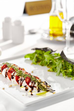 Gourmet, restaurant, delicious dinner food - close up of Caprese Salad. Salad with Tomatoes, Mozzarella Cheese, Balsamic. Salad Dressing with Pesto Sauce and Rocket Salad