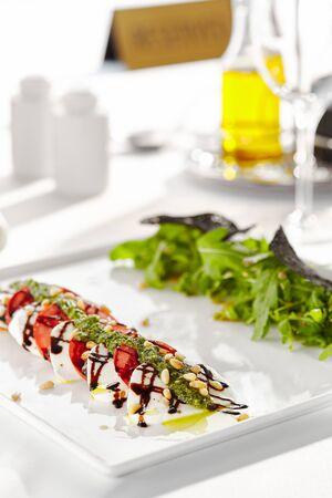 Gourmet, Restaurant, leckeres Abendessen - Nahaufnahme von Caprese-Salat. Salat mit Tomaten, Mozzarella, Balsamico. Salatdressing mit Pestosauce und Rucolasalat