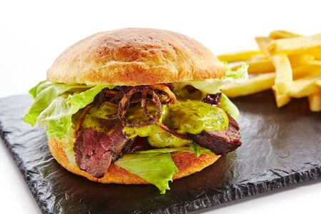 Classic Roast Beef Burger with Mustard, Fried Onions, Lettuce, Green Salsa Verde Sauce and French Fries Garnish. Beefburger with Medium Rare Steak on Natural Black Stone Plate Isolated on White Stock Photo
