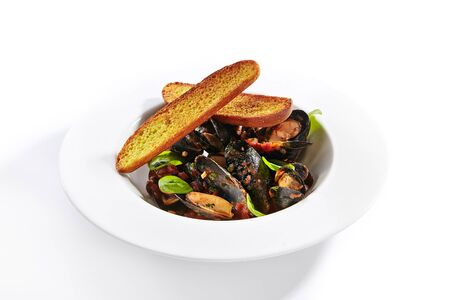 Mussel in red spicy sauce top view. Seafood with crunchy baguette slices in plate. Marine food with roasted bread and basil leaves meal ingredients. French dish isolated on white background Stock fotó