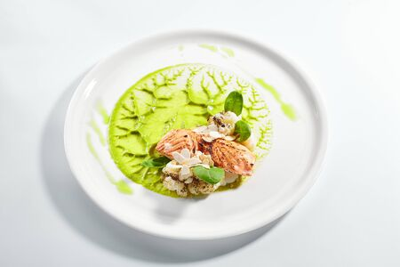 Salmon steak on plate closeup. Red fish piece with green pea puree and cauliflower. Salmon with creamy sauce and vegetables isolated on white background. Restaurant tasty dish, cooked healthy meal Reklamní fotografie