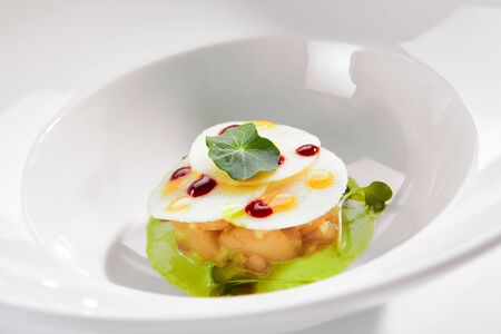 Exquisite serving scallop in pesto sauce with mozzarella on white restaurant plate isolated.