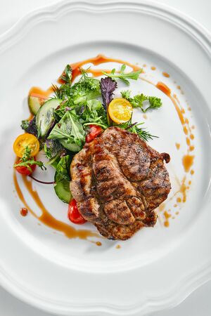 Top view of pork neck steak with mixed salad on white restaurent plate isolated. Restaurant main course with well done meat, veal or beefsteak with tomatoes, fresh parsley, dill and chard topview Stock fotó