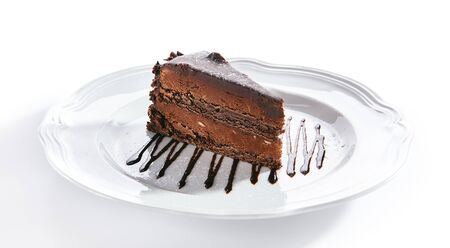 Macro photo of chocolate cake or sachertorte on white blurred background isolated. Triangular slice of brown cocoa biscuit tart decorated with chocolate sauce closeup, selective focus