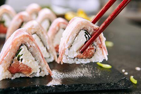 Macro shot of eating bacon uramaki sushi rolls with rice, cream cheese, smoked salmon, pork lard, cucumber, green onions, nori. Holding sushi rolls with chopsticks in Japanese restaurant closeup Stock fotó