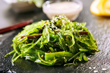 Macro shot of hiyashi wakame chuka or kelp salad on natural black slate plate background. Seaweed food salat with sesame and nut sauce in Japanese restaurant closeup