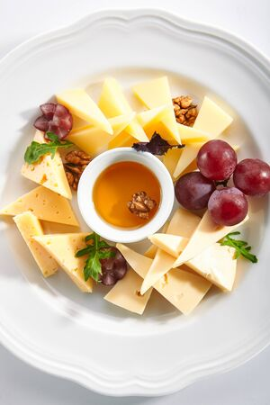 Top view of cheese platter with honey, nuts and red grapes on white restaurant plate isolated. Cheese course with mix of yellow gouda, edam and emmental cheeses topview Stock Photo