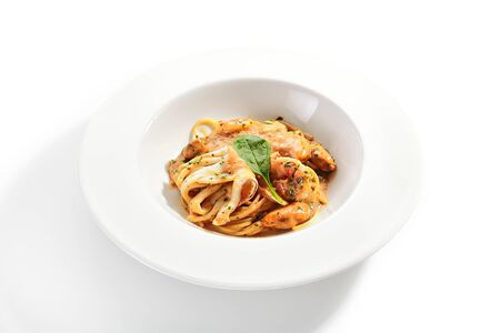 Exquisite serving crispy argentine shrimp, squid with mussels and spaghetti in hot sauce on white restaurant plate isolated. High cuisine restaurent dish with delicious seafood pasta closeup Zdjęcie Seryjne