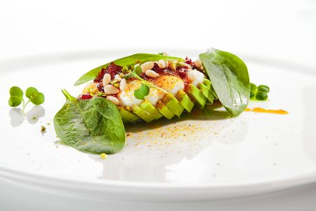 Exquisite serving avocado with mozzarella cream and dried tomato jam on white restaurant plate isolated. High cuisine restaurent exotic dessert with alligator pear in minimalist style closeup