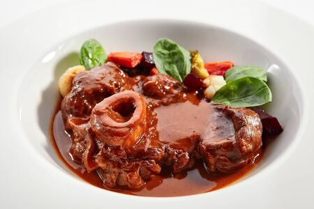 Ossobuco dish closeup. Veal shank with steamed veggies isolated on white background. Beef with demi glace sauce. Italian traditional cuisine. Served and plated delicious food composition