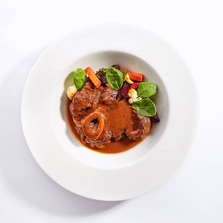 Ossobuco dish top view. Veal shank with steamed veggies isolated on white background. Beef with demi glace sauce. Italian traditional cuisine. Served and plated delicious food composition Archivio Fotografico