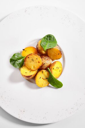 Baked potatoes with herbs dish top view. Baked vegetable with basil leaves isolated on white background. Roasted delicious rural food. Meal garnished with spices on round plate composition