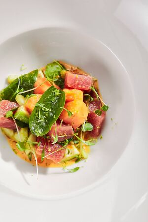 Exquisite serving tuna fillet and papaya salad in spicy sauce on white restaurant plate isolated. High cuisine restaurent dish with delicious yellowfin sashimi tartar in minimalist style topview Stock fotó