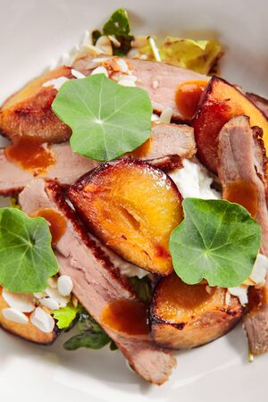 Exquisite serving salad with roasted duck breast, baked pear and strachatella cheese on white restaurant plate isolated. High cuisine restaurent dish with delicious grilled meat and fruits topview Stock fotó