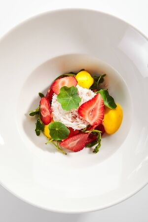 Exquisite serving ripe tomato salad with strawberries, crab meat and strachatella cheese on white restaurant plate isolated. High cuisine restaurent dish with delicious seafood and fruits topview Stock fotó