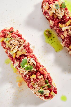 Exquisite serving beef tartare on toast with pickles and black garlic cream on white restaurant plate isolated. High cuisine restaurent dish, minced veal steak meat in minimalist style Stock fotó