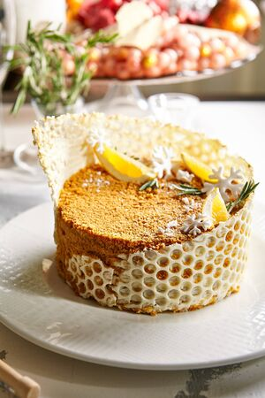 Christmas Honey Cake on Blurred Background. Exquisite Serving Cake Medovik Decorated with Pieces of Lemon, Rosemary, Honeycomb and Snowflakes Made of White Chocolate Close Up Stockfoto