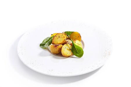Baked potatoes with herbs dish closeup. Baked vegetable with basil leaves isolated on white background. Roasted delicious rural food. Meal garnished with spices on round plate composition