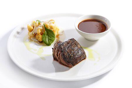 Filet Mignon Steak mit Blumenkohlgericht hautnah. Gebackenes Rindfleisch mit Pfefferkornsauce. Gebratenes Fleischstück lokalisiert auf weißem Hintergrund. Gourmet-Mahlzeit garniert mit Kräuterblättern auf Teller-Komposition Standard-Bild