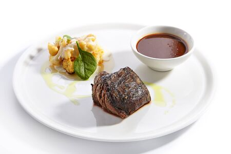 Filet mignon steak with cauliflower dish close up. Baked beef with peppercorn sauce. Roasted meat piece isolated on white background. Gourmet meal garnished with herbs leaves on plate composition Stock Photo