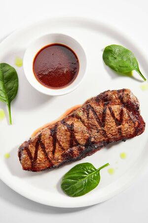 Striploin steak with sauce top view. Grilled beef with basil leaves isolated on white background. Barbeque meat, roasted pork served on plate composition. Traditional New York strip steak
