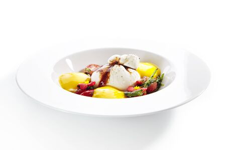 Exquisite serving burrata cheese with tomatoes and mango mousse decorated with flowers on white  plate.