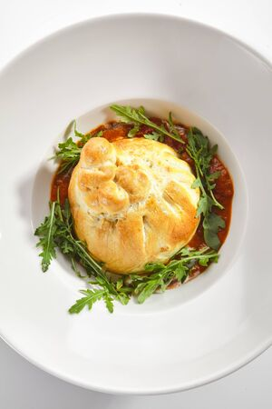 Baked burrata cheese with tomato sauce and fresh arugula leaves on white restaurant plate top view isolated.